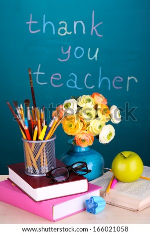 School supplies and flowers on blackboard background with inscription Thank you teacher - stock photo