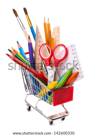School supplies: assorted crayons, paintbrushes, pencils, pastels, rulers and notebook in a shopping cart, isolated on white background  - stock photo