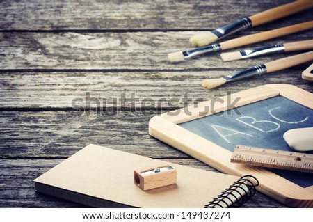 School supplies in brown tone on wooden desk - stock photo