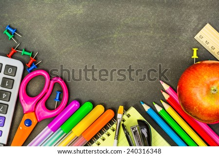 School supplies on a blackboard, can be used as background - stock photo