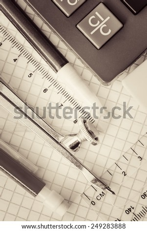 School supplies on a checked notebook background toned in sepia
