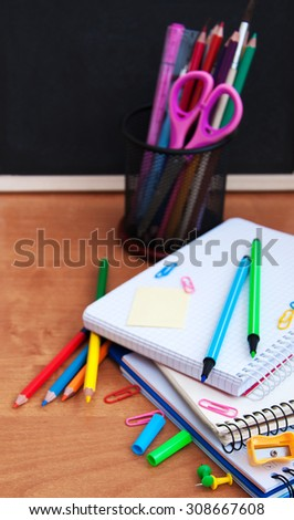 school supplies on a wooden table and  blackboard - stock photo