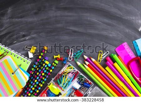 School supplies on blackboard background - stock photo