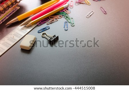 School supplies on blackboard background. Back to school concept with space for text. Notebook stack, pens and pencil. Schoolchild and student studies accessories. Back to school concept. Toned image. - stock photo