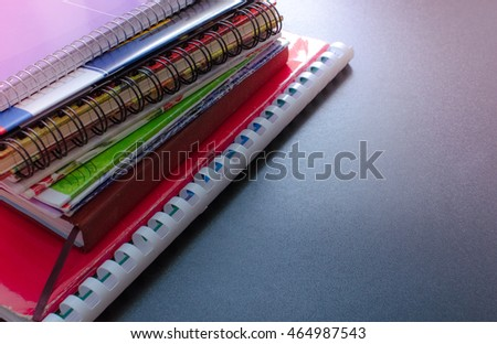 School supplies on blackboard background. Back to school concept with space for text. Notebook stack, pens and pencil. Schoolchild and student studies accessories. Back to school concept. Toned image.