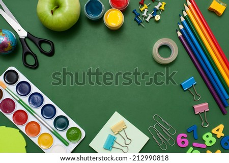 School supplies on blackboard background. Empty space in the middle of green blackboard. Education concept  - stock photo