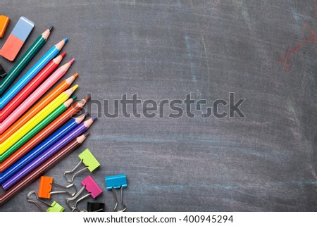 School supplies on blackboard background. Top view with copy space - stock photo