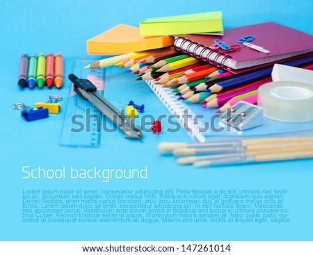 School supplies on blue background - stock photo