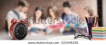 School supplies on desk against happy students standing and reading - stock photo