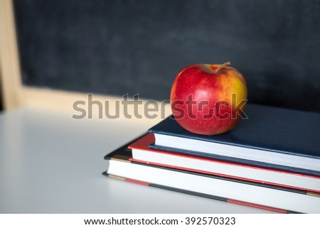 School supplies on old wooden table, near blackboard, close up