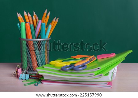 School supplies on table on board background