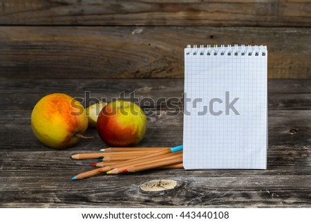 school supplies on wooden background, Notepad, pencils and apples - stock photo