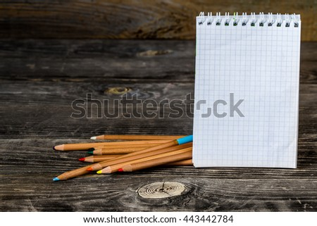 school supplies on wooden background, Notepad with pencil - stock photo