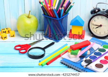 school supplies pencils crayons colorful assortment wooden background gentle blue tone