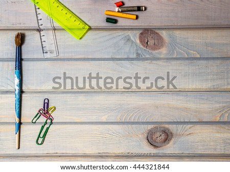 School supplies. Stationery on old wooden background. Top view. Copy space. Paper clips, crayons, rulers and used brush.