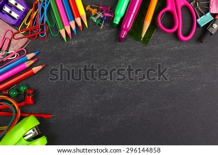 School supplies top corner border on a chalkboard background - stock photo