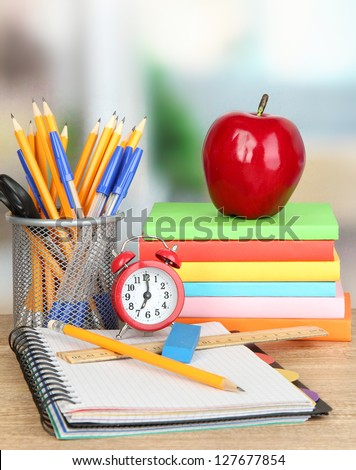 School supplies with apple and clock on wooden table - stock photo