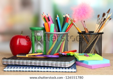 School supplies with apple on wooden table - stock photo
