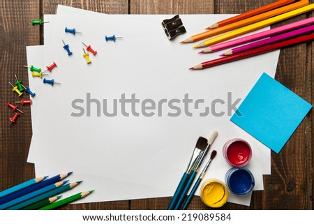 School supplies with blank on wooden background. Copyspace - stock photo