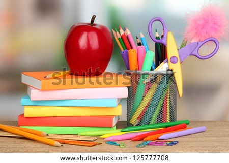 School supplies with books and apple on wooden table