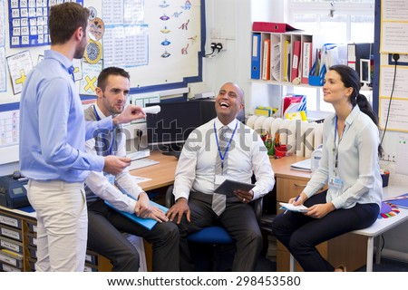 School teachers gather in a small school office for a chat. They look happy. A woman and three men group together. - stock photo