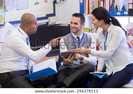 School teachers gather in a small school office for a chat. They look happy. A woman and two men group together. A man holds a digital tablet