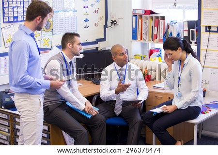 School teachers gather in a small school office for a chat. They look serious. A woman and three men group together. The woman holds her hand to her head.