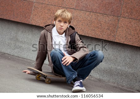 School teen sits on skateboard near school, day