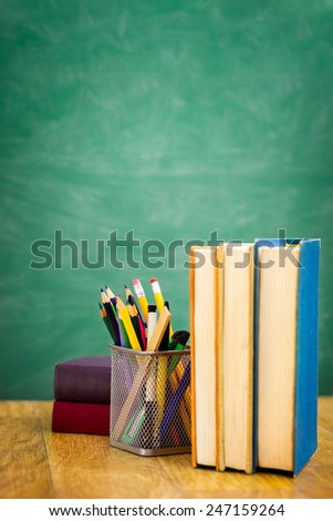 School textbooks on a desk in front of empty  blackboard - stock photo