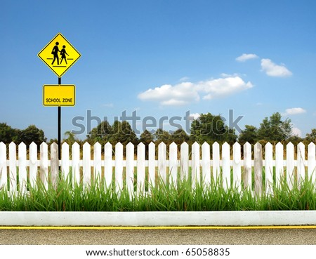 School warning sign with white fence and blue sky - stock photo