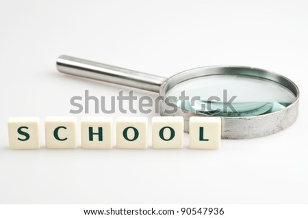 School word and magnifying glass - stock photo