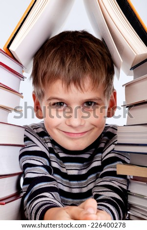 Schoolboy and a heap of books isolated on a white background - stock photo