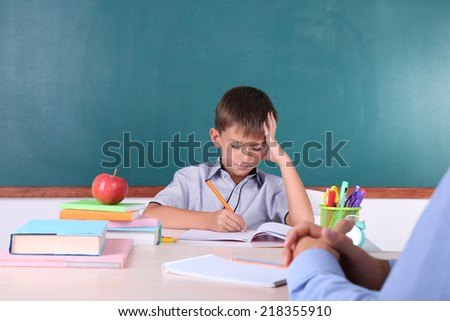 Schoolboy and teacher sitting in classroom on blackboard background