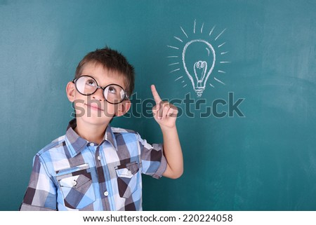 Schoolboy at blackboard in classroom - stock photo