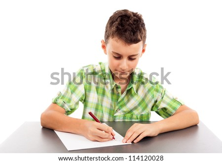 Schoolboy at exam writing at his desk, isolated on white background - stock photo