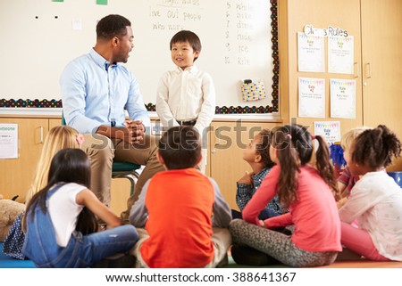Schoolboy at front of elementary class with teacher