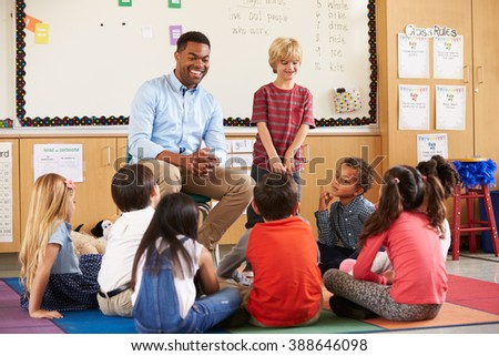 Schoolboy at the front of elementary class with teacher - stock photo
