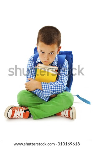 Schoolboy bored, frustrated and overwhelmed by studying homework. Little boy sitting down on floor isolated on white background.  - stock photo