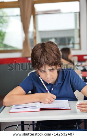 Schoolboy cheating at desk during examination in classroom