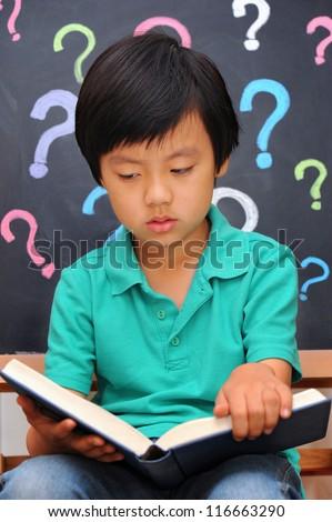Schoolboy dislikes reading book - stock photo