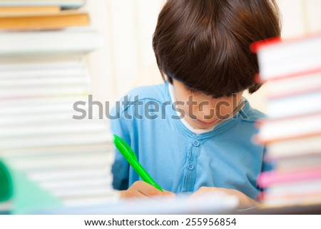 schoolboy doing homework in the library. copy space - stock photo