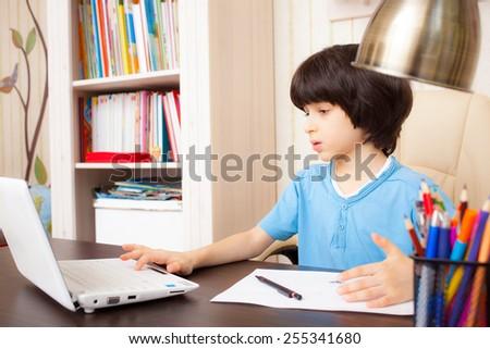schoolboy doing homework on notebook, portrait - stock photo