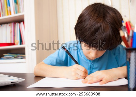 schoolboy doing homework, portrait - stock photo