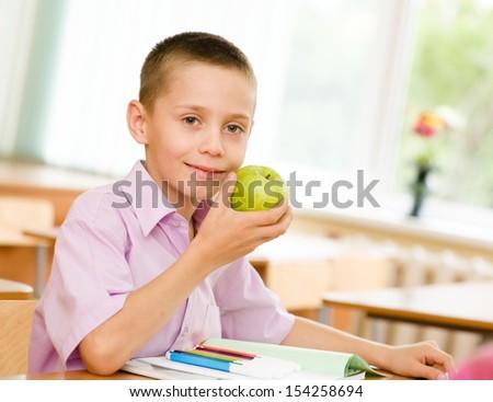 schoolboy eating an apple - stock photo