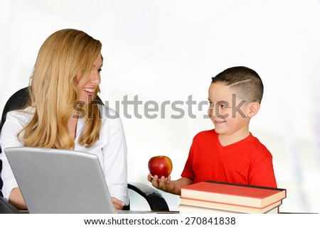 Schoolboy giving red apple to his teacher - stock photo