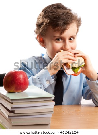 Schoolboy having a sandwich and an apple during his lunch break