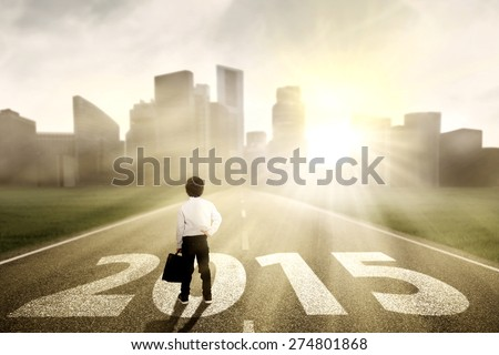 Schoolboy holding briefcase standing on the road and looking the future 2015 - stock photo
