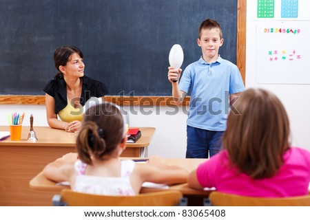 Schoolboy holding light bulb in front of class, representing a big idea he has