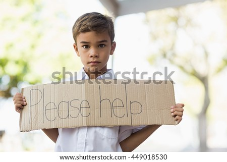 Schoolboy holding placard which reads please help at school - stock photo