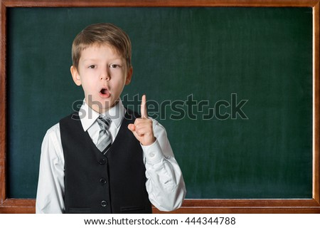 Schoolboy  in front of a green chalkboard showing finger upward. Education and school concept - stock photo
